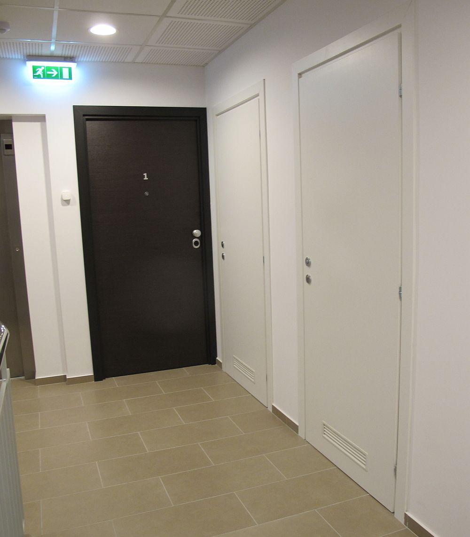 Usile albe de pe holuri mascheaza locul contoarelor pentru fiecare apartament