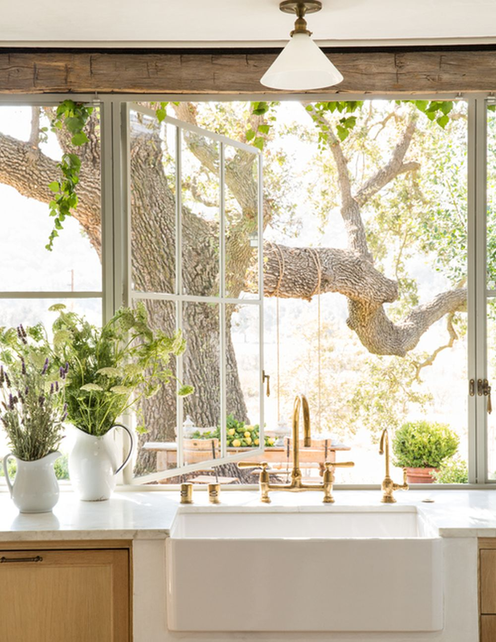 Kitchen sink and counter against large window looking out to green garden, wooden drawers, white frosted glass lighting fixtures