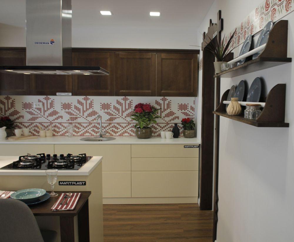Pe peretele bucătăriei este o placare imprimată la Martplast cu motive tradiționale supradimensionate.