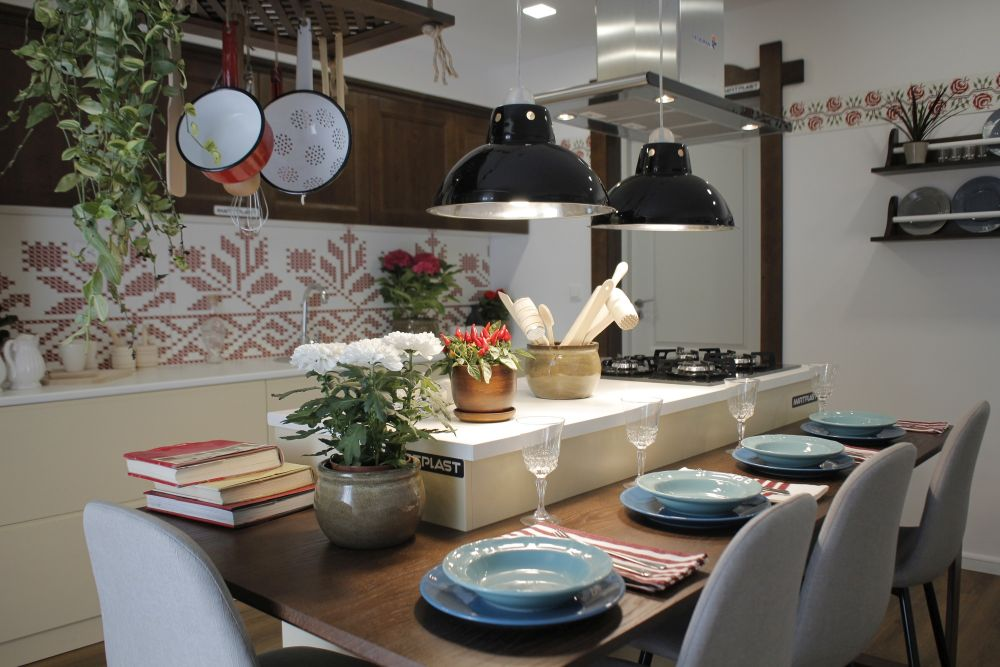 În centrul bucătăriei este masa insulă ce include locul de gătit și locul de luat masa.