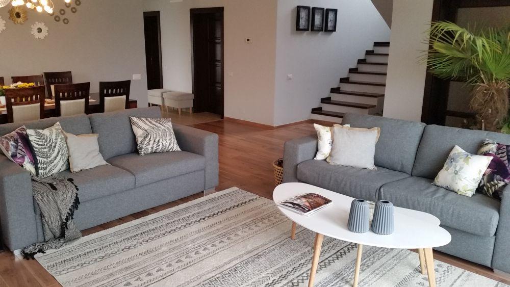 Din living se vede și scara interioară care duce la etaj, iar în spatele canapelei din dreapta este intrarea la bucătărie.