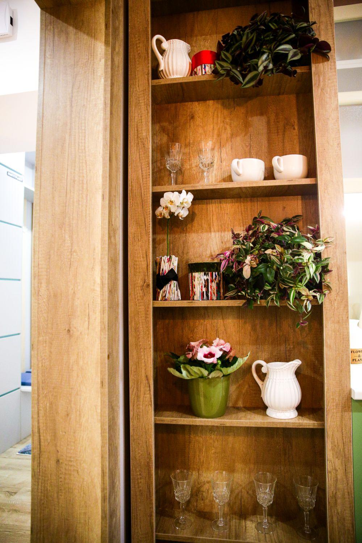 Către hol, mobila de bucătărie este terminată cu o etajeră.