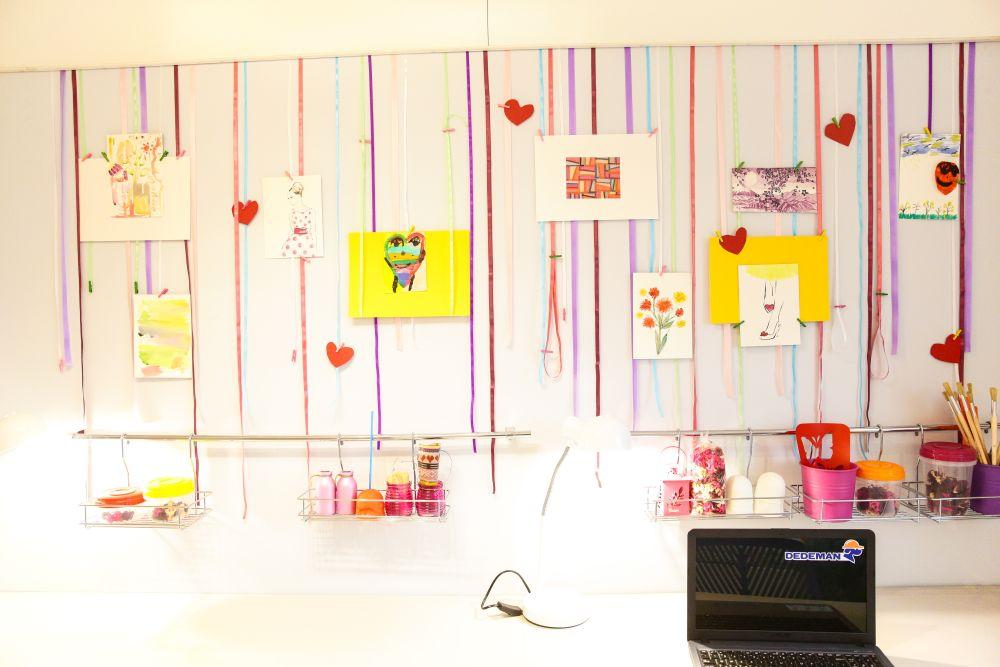 Deasupra biroului am creat o zonă de afișare cu panglici. Practic am lipit panglici pe o bucată lungă de PAL fixată la rîndul ei în perete. De aceste panglici fete pot agăța desene și alte lucruri din hârtie. Este o soluție simplă, dar d emare efect vizual, grație culorilor panglicilor.