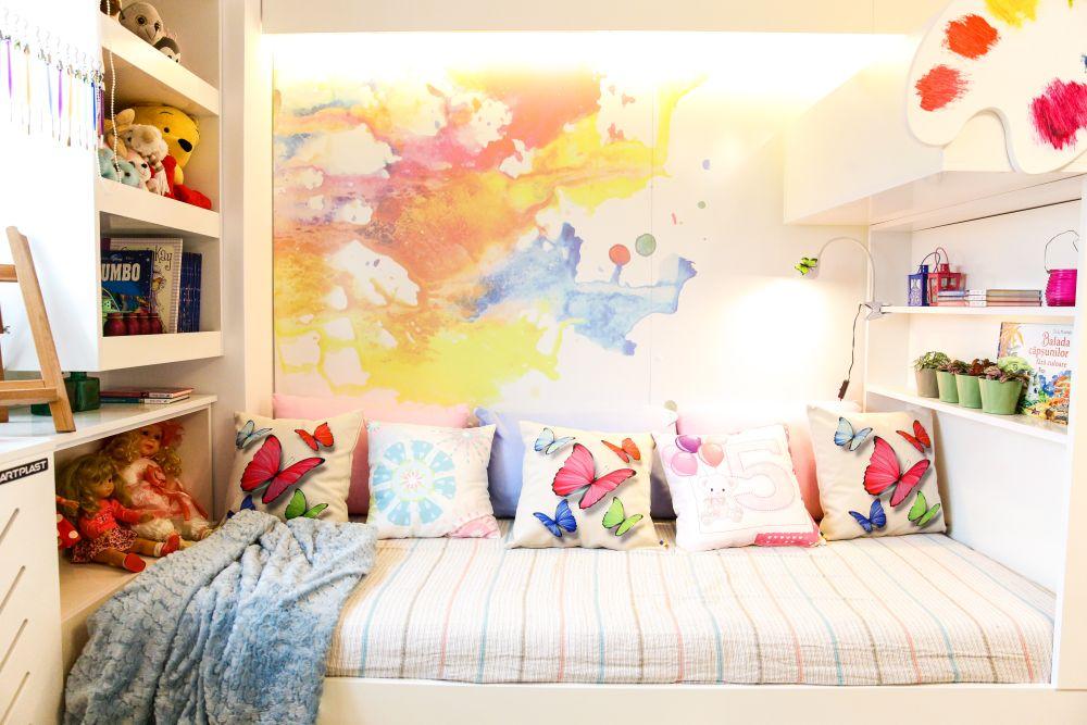 Placarea de perete din zona patului este imprimată cu un desen abstract, dar colorat care înveselește camera.