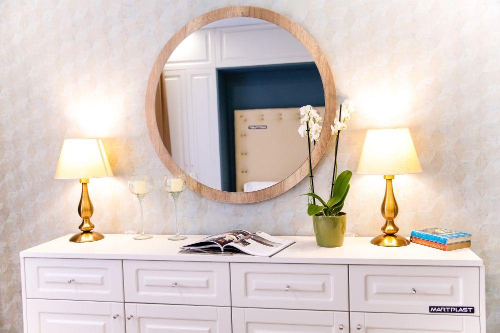 În fața patului există o comodă cu sertare și o oglindă rontudă.