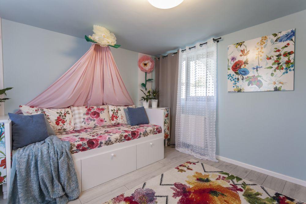 Înălțimea camerei nu este foarte generoasă, de aceea am încercat să prevăd elemente pe verticală - draperii, perdele, placări de o parte și de alta a patului, baldachinul. Tablourile de pe perete sunt realizate la Martplast, covorul și decorațiunile textile sunt de la Dedeman.