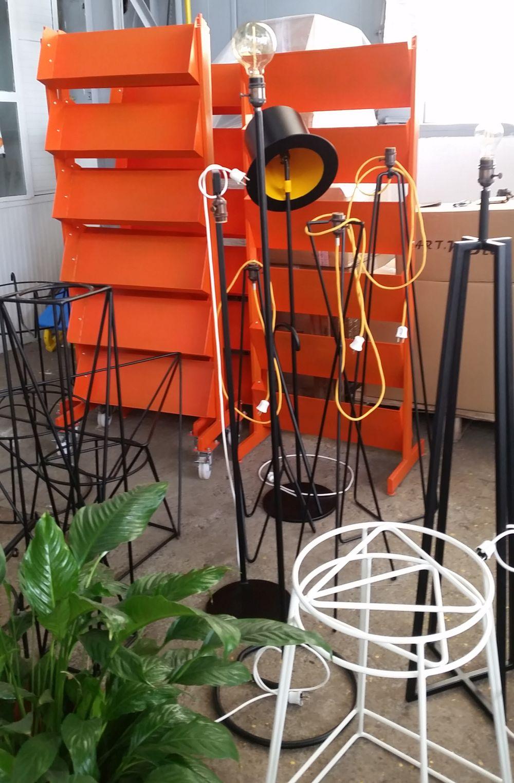 Rafturile acestea portocalii din spate pe roți sunt și ele produse la AktDecor. Au o gamă de produse dedicată pentru expunerea de produse, adică pentru firme.