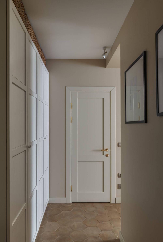 Holul cu dualpuri și în fundal ușa de acces la baie.