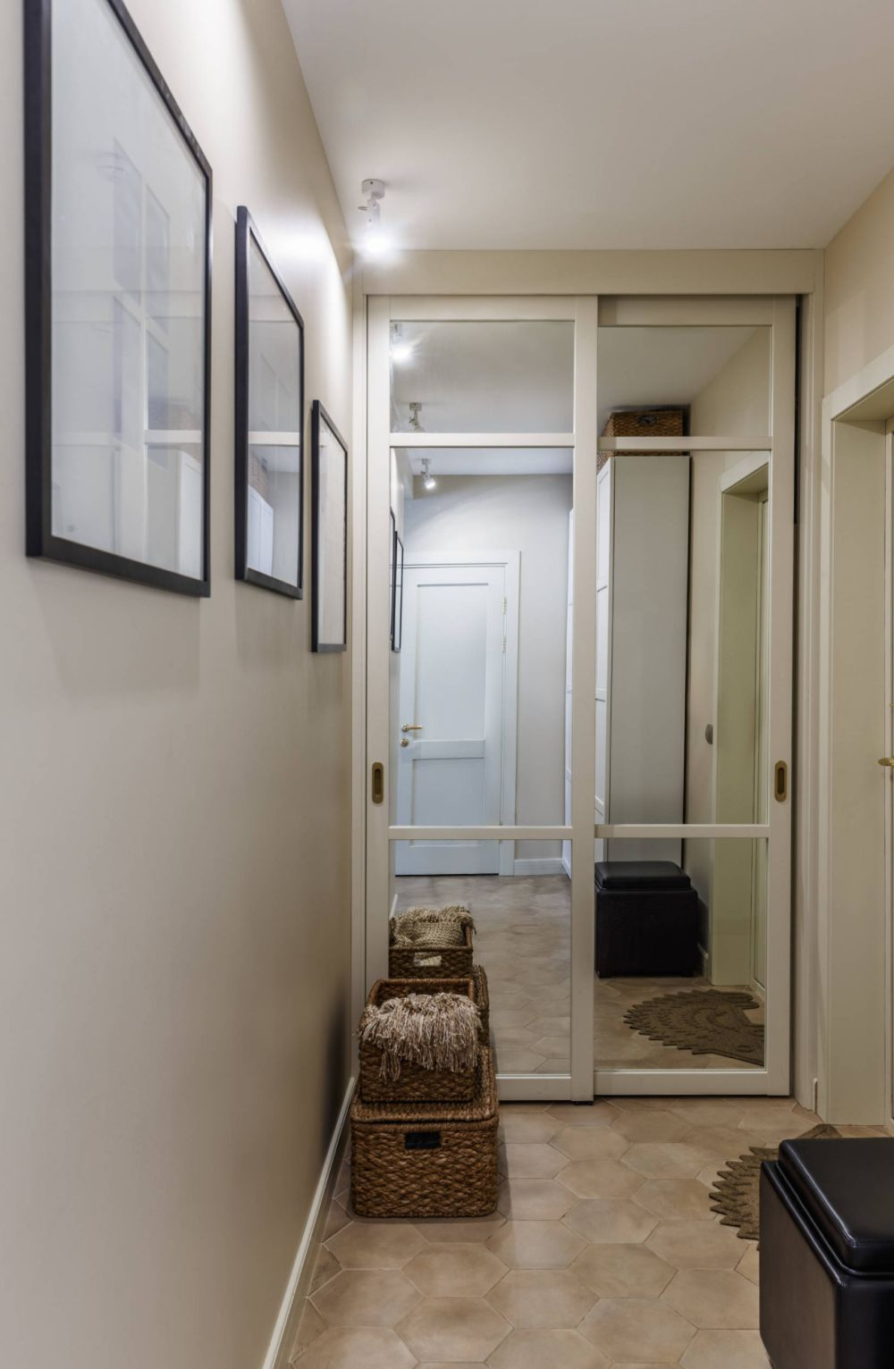 În spatele ușii de la intrarea în locuință este un alt dulap, de această dată placat cu oglinzi și cu rol de cuier și pantofar.