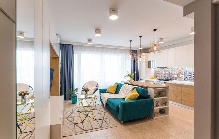 Încă de la intrarea în locuință se vede spațiul zonei de zi cu locul de canapea în spatele căreia este organizată bucătăria.