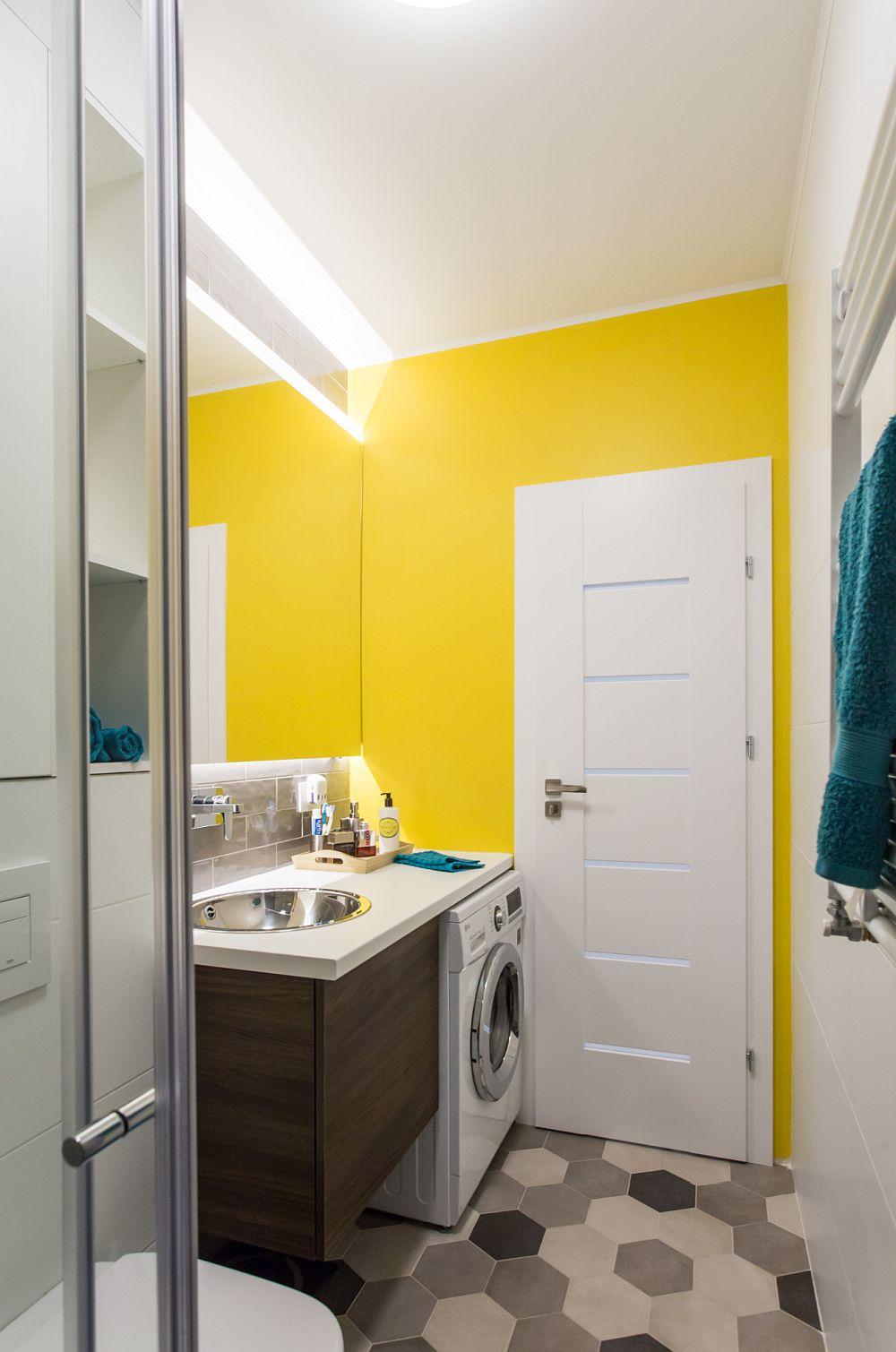 Pentru un strop de culoare în baie, peretele din dreptul ușii interioare a fost vopsit într-un galben solar. Culoarea contează în atmosfera camerei pentru că dă senzația de luminozitate în acest spațiu mic.
