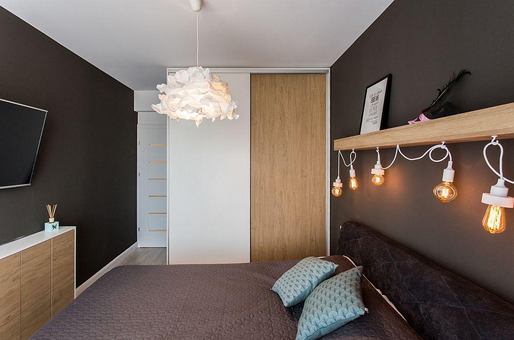 În spațiul dormitorului designerii au prevăzut un dulap exact cât lățimea peretelui din zonă. Pentru a nu încărca spațiul, au gândit dulapul ca pe o placare în două texturi, una de lemn și una albă (albul a fost poziționat în relație cu ușa de interior albă). Contrastul dintre lemn și findul negru al peretelui din zonă dă foarte bine și produce un efect de căldură în cameră.