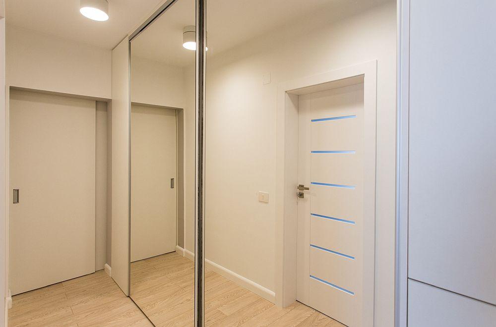 Pentru ca spațiul holului să nu se simtă prea claustrofobic, designerii au prevăzut ca ușile culisante ale ansamblului de depozitare să fie placate cu oglinzi.