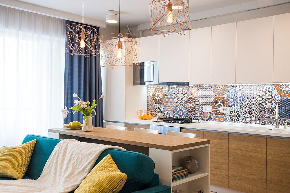 Partea inferioară a anamsalului bucătăriei este aproapiată ca și nuanță de cea a parchetului, iar corpurile suspendate sunt deschise la culoare pentru a nu încărca vizual spațiul.