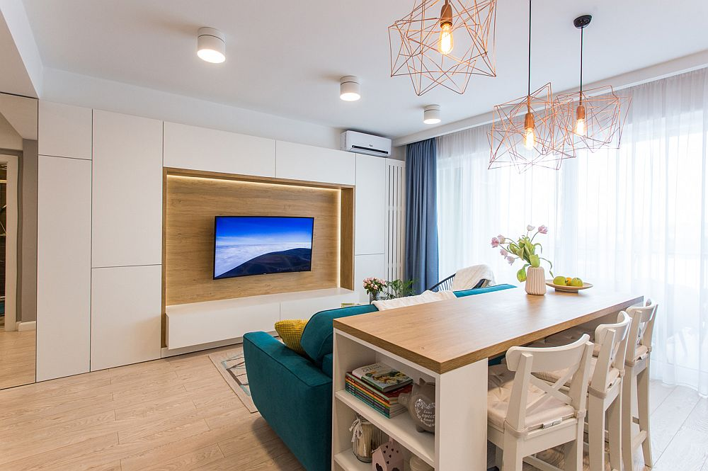 Iluminatul din zona de zi este gândit pe zone și are atât rol funcțional pentru asigurarea vizibilității, cât și unul decorativ (banda LED). Corpurile de iluminat sunt achizționate de la Nova Ambient din Oradea, conform indicațiilor designerilor.