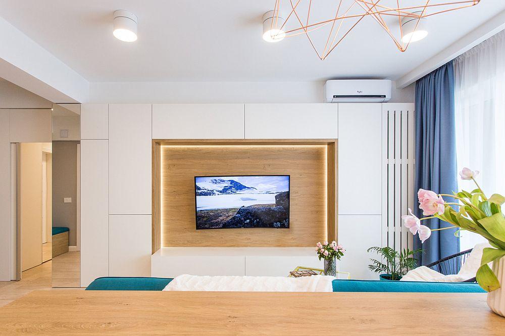 Mobila din living este funcțional și minimalist tratată. Golul lăsat pentru televizor este evidențiat printr-o placare cu textură similară lemnului și printr-un iluminat LED: Toate cablurile aferente televizroului sunt mascate în spatele acestuia, lucru de care s-a ținut cont încă din faza de proiect.