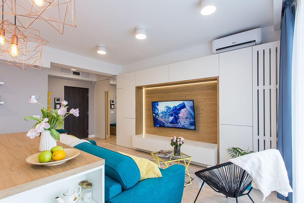 În living caloriferul înalt dispus ăn lateralul ferestrelor generoase este mascat în ansamblul mobilierului. Designerii au prevăzut înălțimea mobilierului în relația cu grinda vizibilă în zona de intrare în casă. Astfel a exista și loc suficient ca deasupra ansamblului să fie poziționat aparatul de aer condiționat.