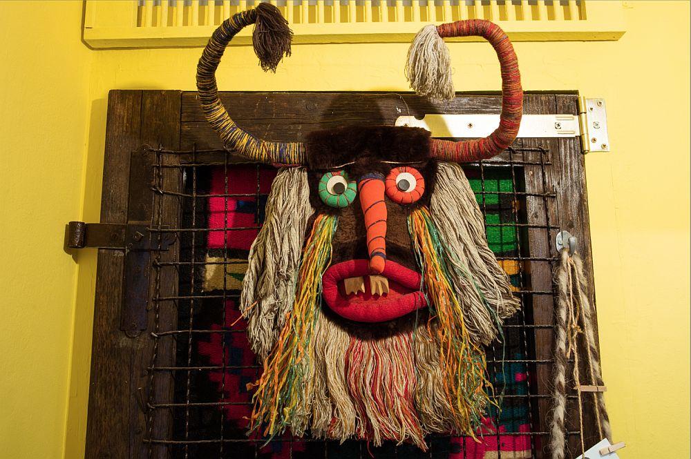 Nișa care există în hol și care poate fi folosită pentru depozitare este mascată de o ușă atipică construită dintr-o plasă de Buzău înrămată cu scândură și accesorizată cu balamale vechi. În spatele ei este prinsă o cuvertură tradițională pentru a masca interiorul nișei. Pe fața ușii este prinsă o mască tradițională, iar de ramă alte agățători pentru haine, genți, obiecte.