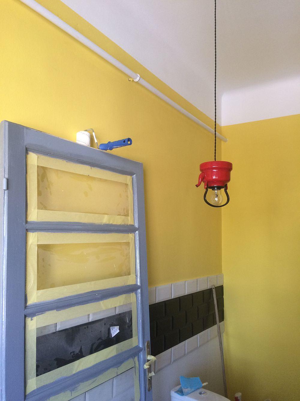 Imagine din faza de șantier. Ușa camerei a fost decapată și apoi revopsită, iar un ceainic vechi roșu a devenit abajur pentru corpul de iluminat de deasupra măsuței.