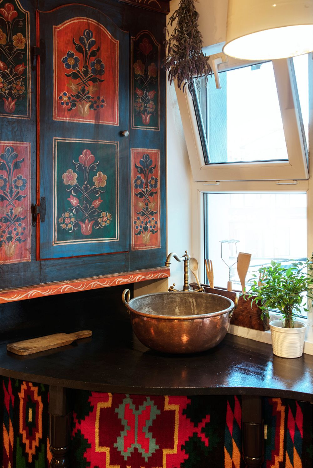 În dreptul ferestrei a fost plasată bucătăria, care este creativ amenajată. Locul pentru chiuvetă este în fața ferestrei fixe, iar în lateral peretele este placat cu uți vechid e dulap pictate din colecția artistei. Ea le-a cumpărat cu ceva ani în urmă de la un târg de vechituri și acum le-a găsit locul. Chiuveta este realizată pe șantier dintr-un vas vechi de la bunica ei.