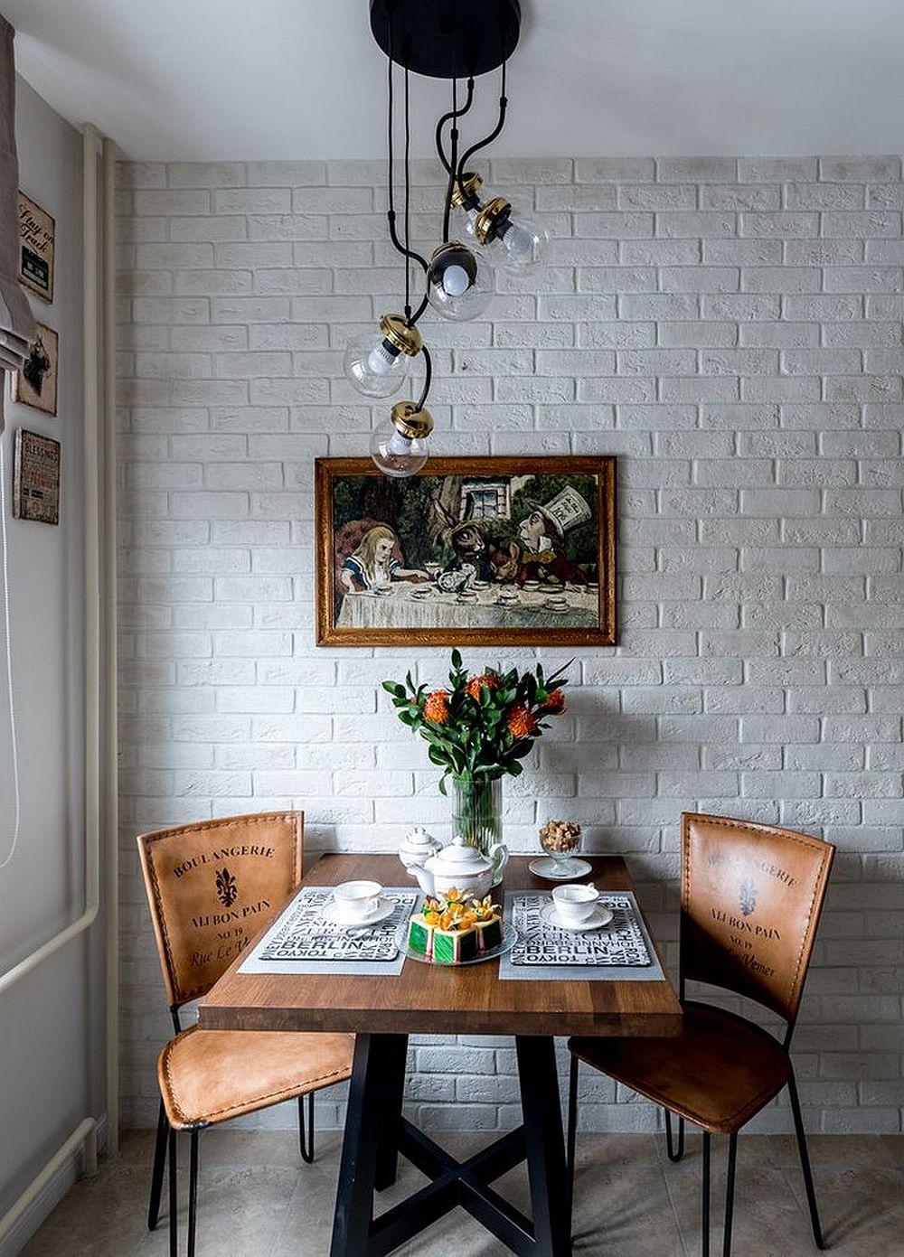 Pentru ca centrul micii bucătării să fie cât mai liber, adică să existe loc în fața frontului de lucru și acces la frigider, masa a fost poziționată alături de perete. Și pentru ca peretele să fie unul rezistent la frecare, inevitabilă cu spătarul scaunelor, designerul a prevăzut o placare cu cărămidă aparentă.