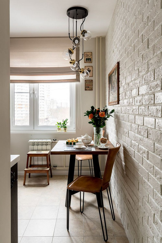 Locul de luat masa din bucătărie după renovare este elegant și actual. Un corp de iluminat marchează zona, iar mobilierul este cu accente industriale.