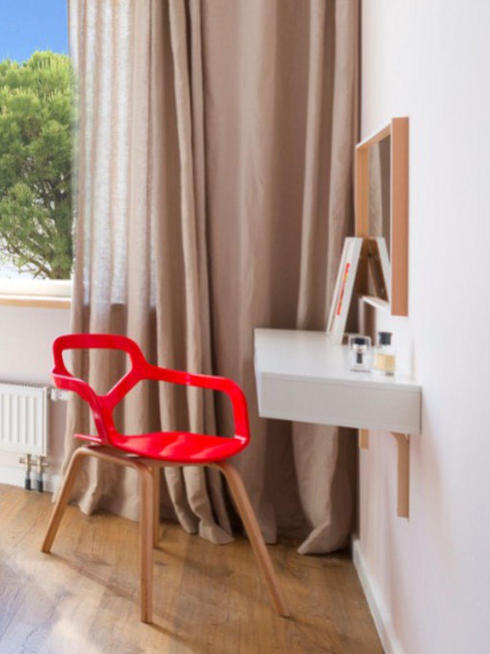 În dormitorul matrimonial s-a dorit și o masă de toaletă. Aceasta este configurată foarte simplu cu un corp cu sertare suspendat și un scaun în zonă. Simplu, funcțional, dar plăcut estetic.