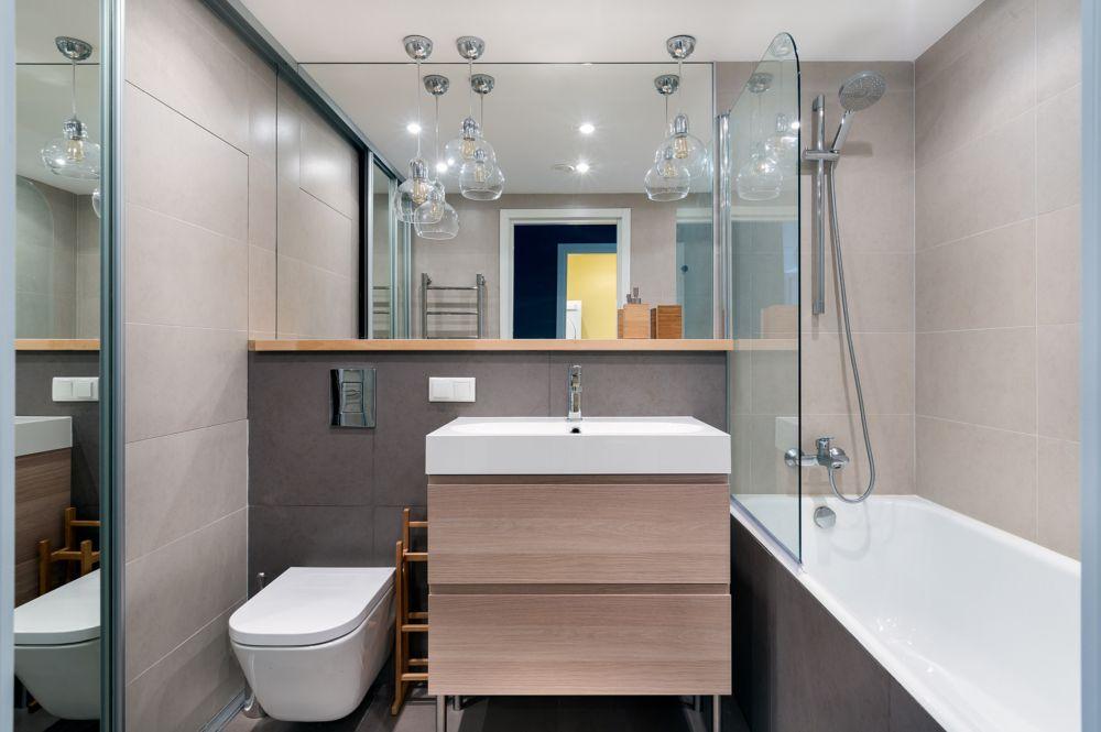 Finisaje simple, neutre ăn baie, dar prezența lemnului la nivelul polițeriși al mobilierului face ca totul să se simtă mai plăcut.