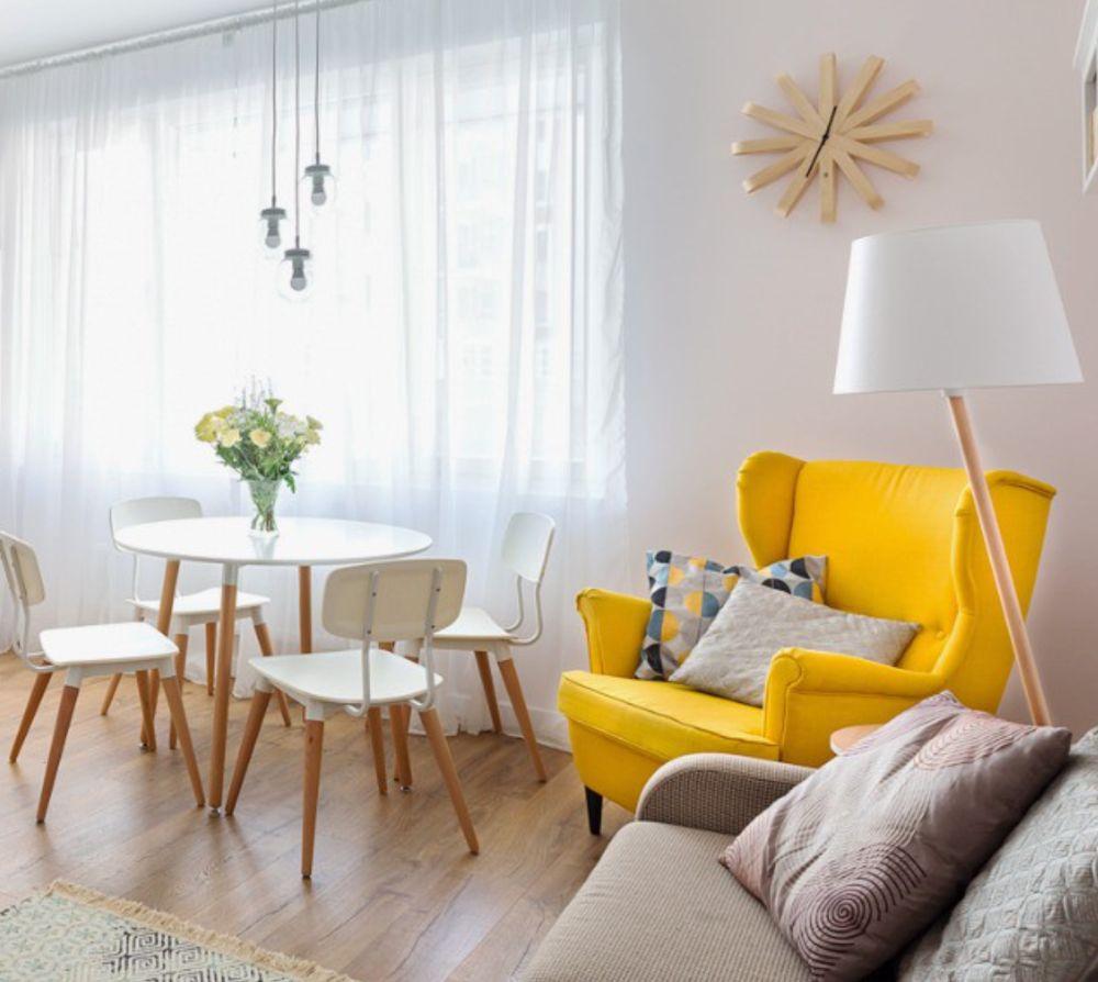 Ambientul camerei de zi este creionat pe suprafețe mari în contrast de nuanțe albe cu texturi similare lemnului. Dar în acest ambient orice pată de culoare contează. fotoliu galben vine să aducă un plus de stălucire și căldură în acest spațiu compact.