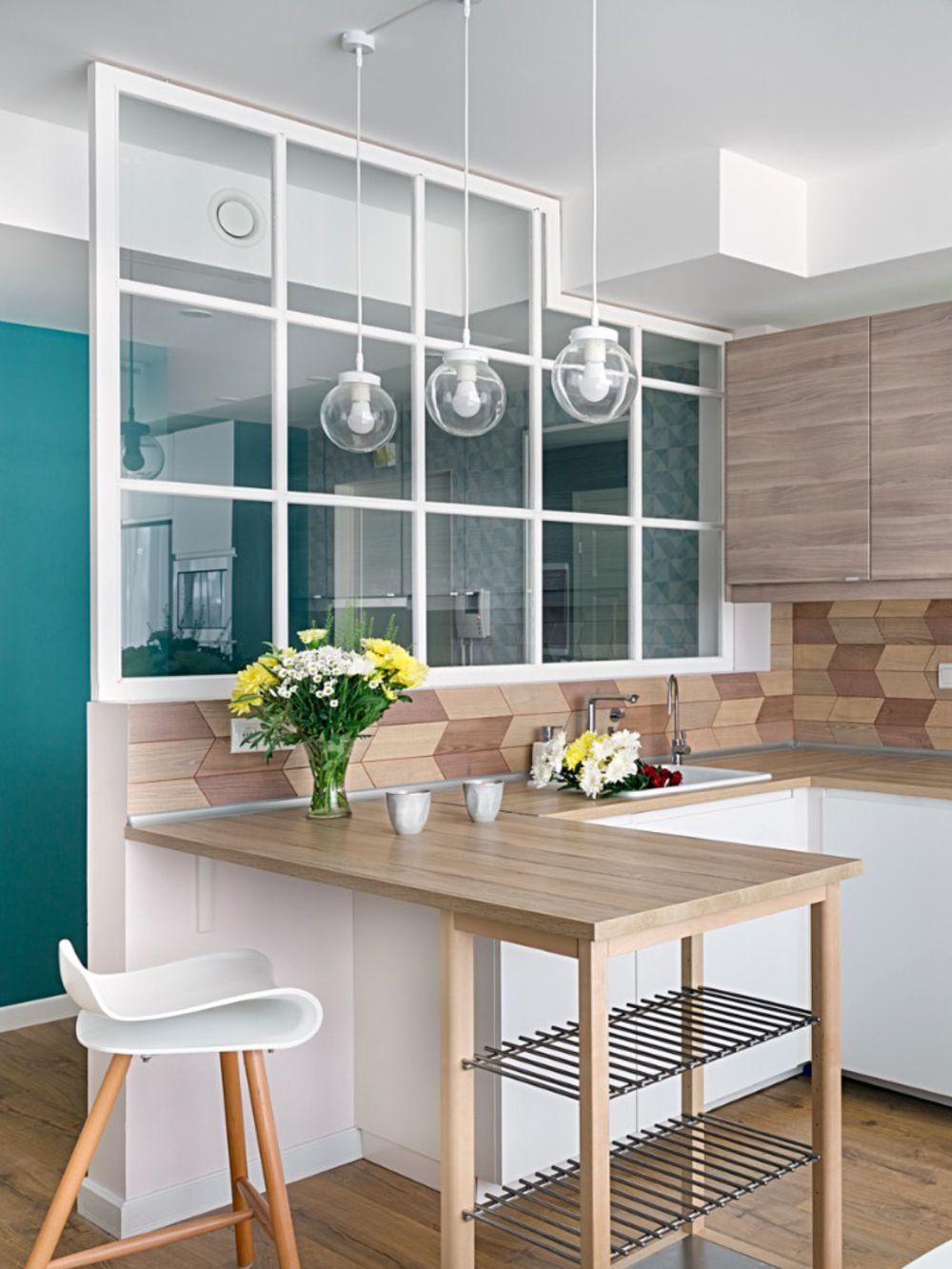 Spațiile în prima parte a locuinței au fost deschise, inclusiv către hol, dar o separare s-a simțit necesară. Astfel, între bucătărie și holul de la intrare există un paravan fix cu panouri de sticlă ce delimitează funcțiunile.
