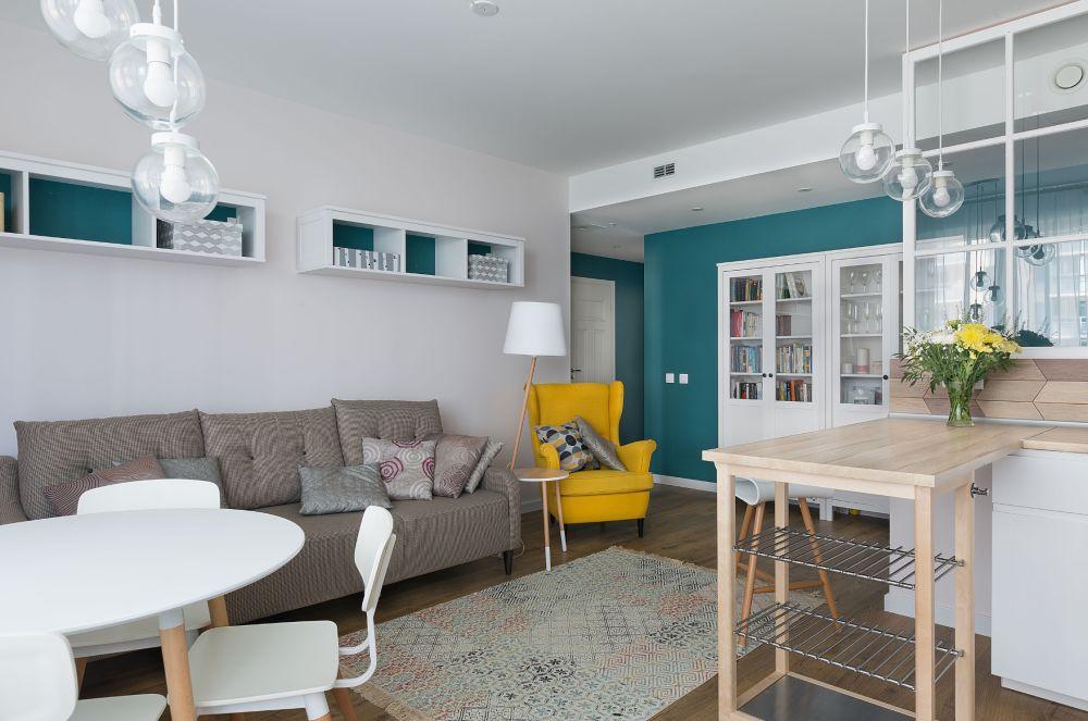 Culoarea închisă și saturată de pe peretele holului, deci pe o suprafață opusă ferestrei, alungă monotonia, dar conferă și senzația de adâncime. În plus pe fundalul ei se văd frumos piesele mari de mobilier albe, dar se creează și un contrast solar cu fotoliul galben. Pentru a face legătura cu peretele turcoaz, designerul a prevăzut ca etajerele de deasupra canapelei să aibă interiorul colorat în aceeași nuanță.