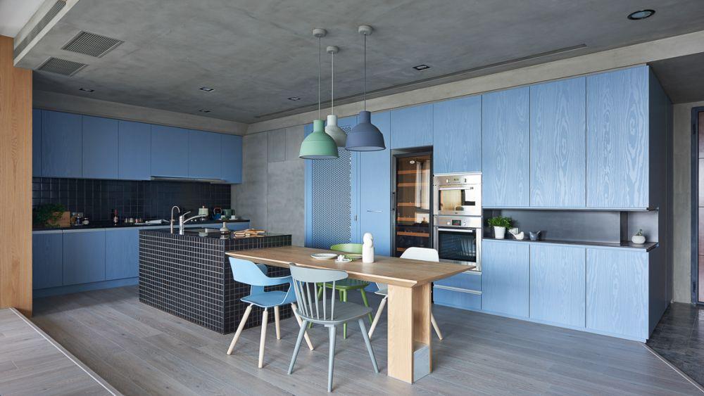 Bucătăria este finisată la nivel de plafon și pereți cu tencuială decorativă care imită betonul, dar în contrast cu aceste finisaje sunt pardoseala caldă, masa sculpturală și elementele similare lemnului care se citesc în ansamblul vitrinei pentru vinuri. Mobila este albastră cu fronturi fără mînere pentru un aspect cât mai curat și orodonat.