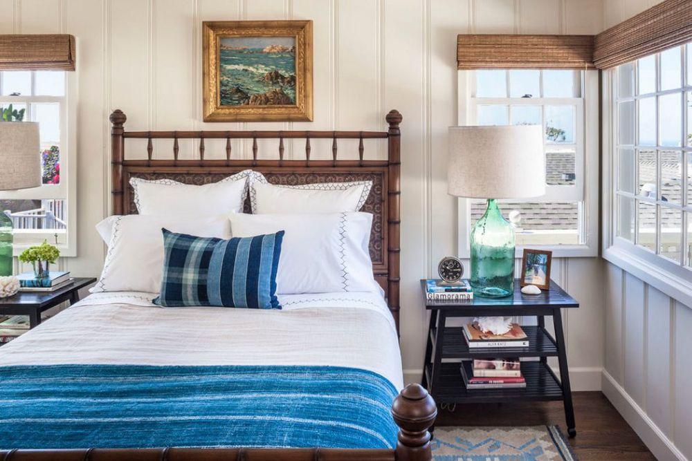 Dormitorul este unul cu multe ferestre, iar stilul cottage se simte prin dimensiunile modeste ale camerei, dar și prin forma tâmplăriei și modul de poziționare al patului în raport cu ferestrele. Tema marină este subliniată prin finisaje (lambriuri) și decorațiuni (tablouri, alb-albastrul lenjeriei de pat și al decorațiunilor textile, rolete de bambus).