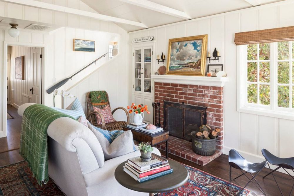 Pentru că este o casă mică, din prima cameră, care este livingul, se accede către bucătărie prin intermediul unui hol. O deschidere simplă, lipsită de artificii de tip arcadă, ce lasă lumina să pătrundă către centrul casei. Scara interioară simplă, zidită și placată precum pereții cu același tip de lambriu. Șemineul din cărămidă refractară se remarcă în acest decor prin contrast cu suprafețele mari de perete și pardoseală, deschise la culoare. Stilul cottage subliniat prin forma mobilierului, prezența cărămizii, a șemineului, iar stilul marin conturat prin lambriurile albe, tablourile și decorațiunile cu temă marina, dar piese mici de mobilier din lemn sau împletituri.