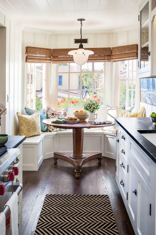Bucătăria are și un loc de luat masa de-a dreptul idilic amenajat în fața ferestrelor bovindoului. În loc de scaune este realizată pe comandă o banchetă simplă cu fronturi frezate, fără tapițerie pentru a nu ocupa prea mult spațiu și pentru a permite o curățare rapidă. Stilul cottage este imprimat prin arhitectura casei, respectiv al spațiului bovindoului, prin designul, culoarea și textura mesei, modelul frezat de la baza banchetei, iar stilul marin este prezent prin rulouri din bambus și lambriurile de pe pereți.