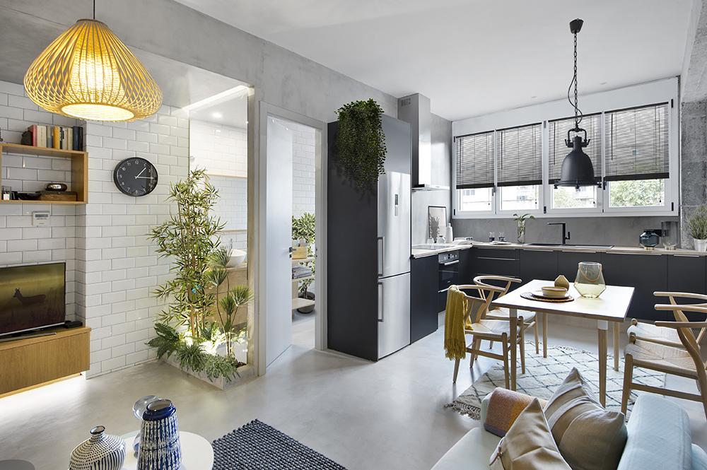 Bucătăria este deschisă către cameră, iar spațiul este gândit astfel încât să existe și un loc generos de luat masa, care atrage atenția, fiind punctat și de un corp de iluminat cu design industrial.