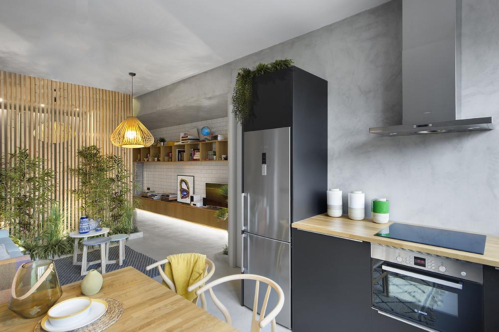 Pentru ca frigiderul să nu apară stingher în ansamblul bucătăriei, el a fost încadrat de un mobilier a cărui înălțime a fost configurată în relație cu grinda din cameră.