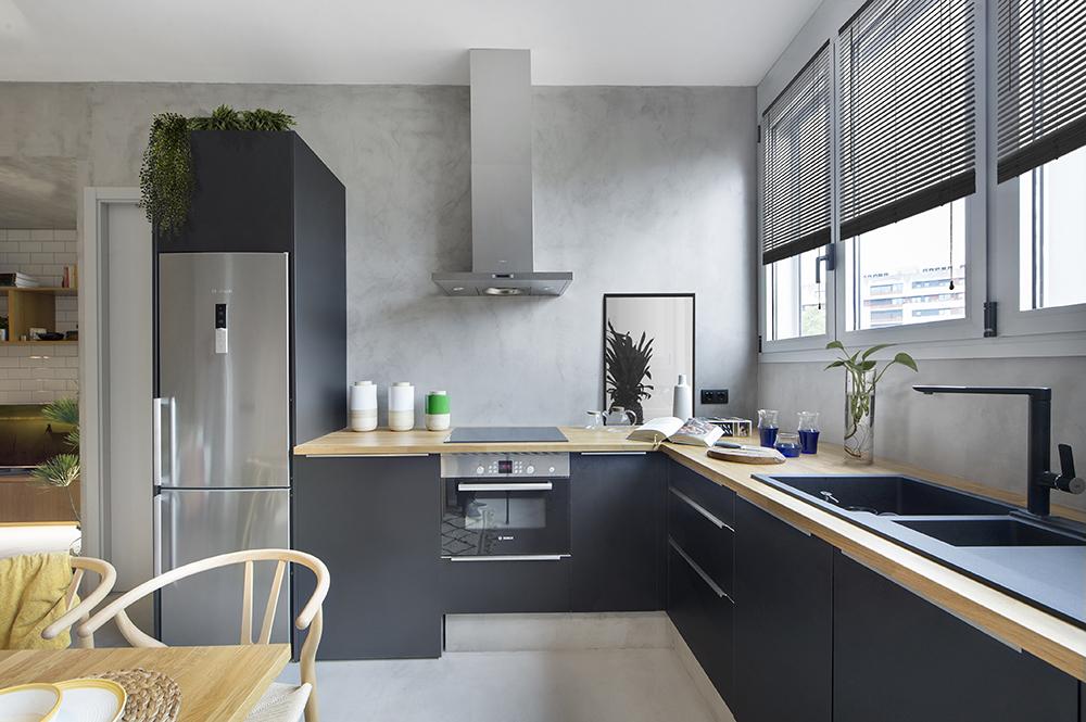 Bucătăria este configurată fără corpuri de mobilier suspendate pentru a nu încărca spațiul, dar și pentru că în zona cu ferestre nu se preta o astfel de soluție.