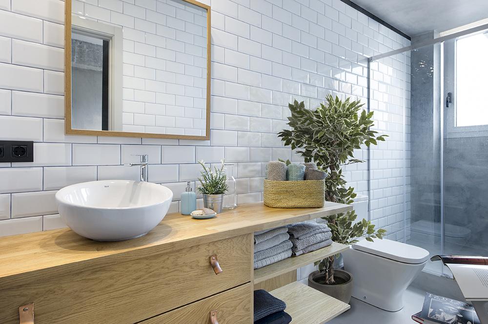 Camera de baie lungă și îngustă are mobilier minimal, dar conceput pentru cât mai multă depozitare, vas wc și duș separat cu panouri din sticlă. Finisjul faianței se continuă și în zona de cameră. Locul mașinii de spălat este mascat în ansamblul bucătăriei.