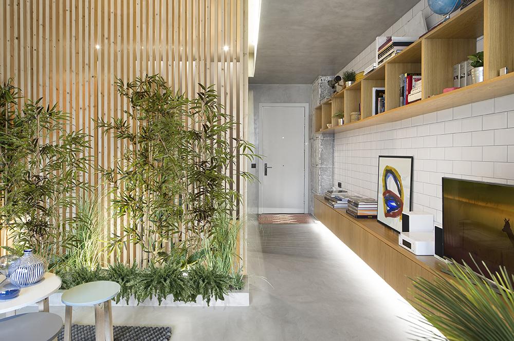 După ușa de la intrare, pe tot peretele disponibil este configurată o comodă și o etajeră, ambele pentru depozitare și expunere. Finisajul ales aici este mai inedit, respectiv plăci de faianță albă ce imită cărămida. Comoda cu corpuri suspendate beneficiază de iluminat cu bandă LED, care asigură un scenariu interesant de lumină pe timpul serii.