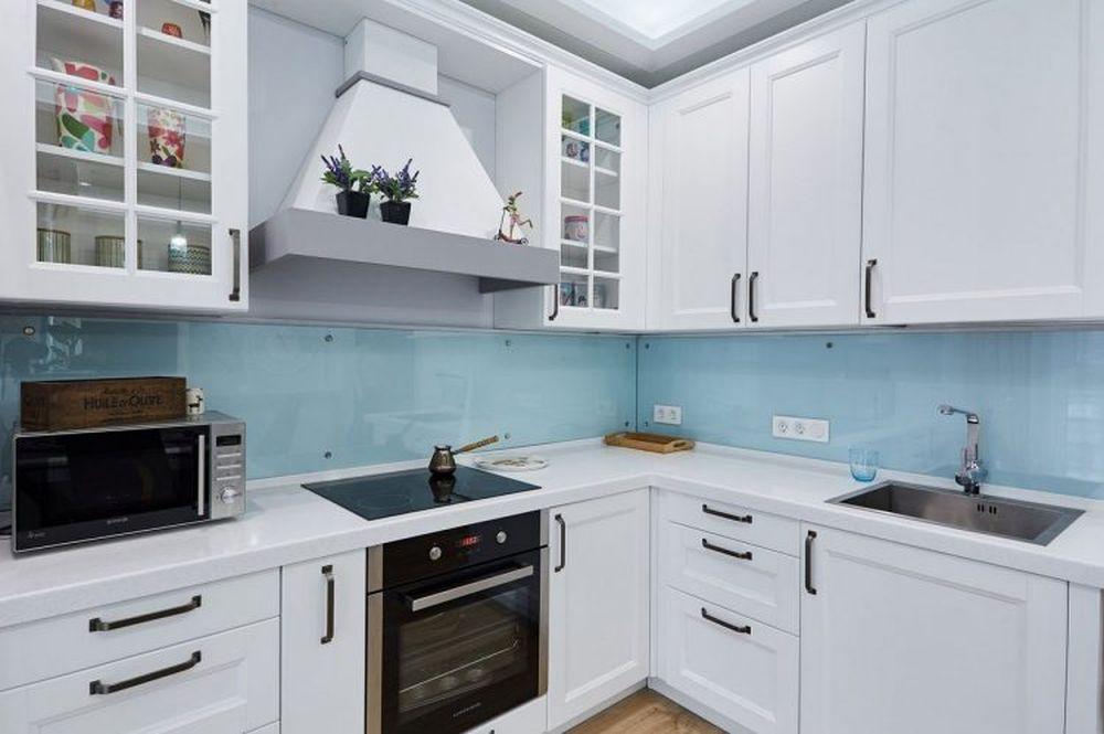 În zona cea mai vizibilă către living, mobila bucătăriei este gândită simetric pentru aimprima senzația de ordine.