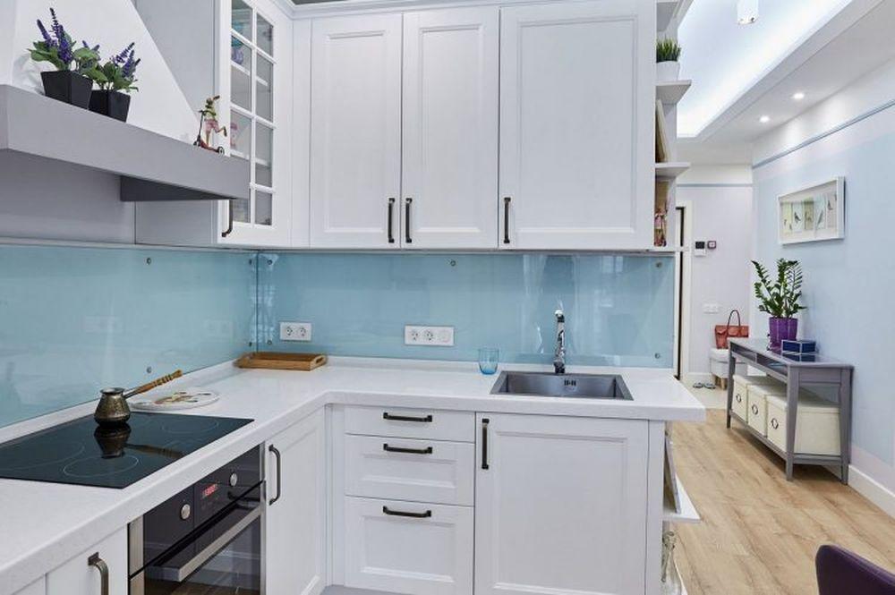 Bucătăria este configurată în L cu suficient spațiu între dotări.