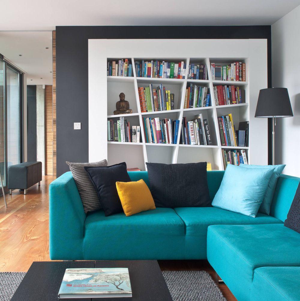 O bibliotecă mai inedită, o culoare mai intensă pentru tapițeria canapelei și camera de zi devine un loc atragător pentru toată familia, care s epoate reuni pentru a viziona împreună filme sau pentru a juca jocuri. Foto Simon Maxwell.