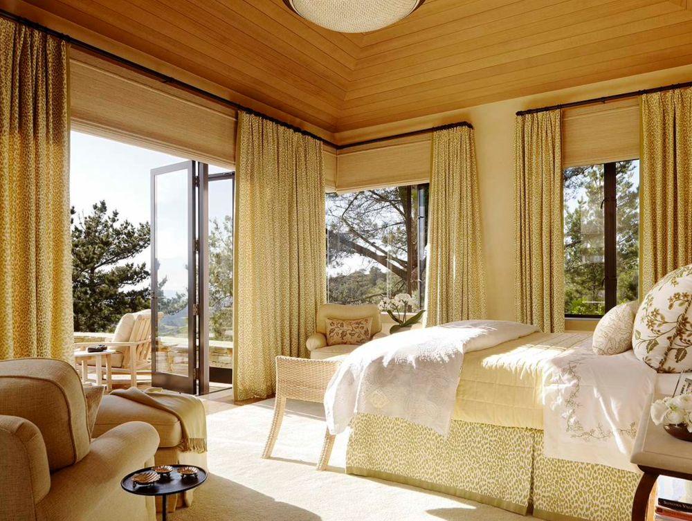Un dormitor matrimonial cu multe ferestre și deschidere către o terasă proprie. Golurile ferestrelor sunt frumos ăncadrate de draperii, aceeași țesătură fiind folosită și pentru lateralele patului. Un decor asortat, studiat, elegant.