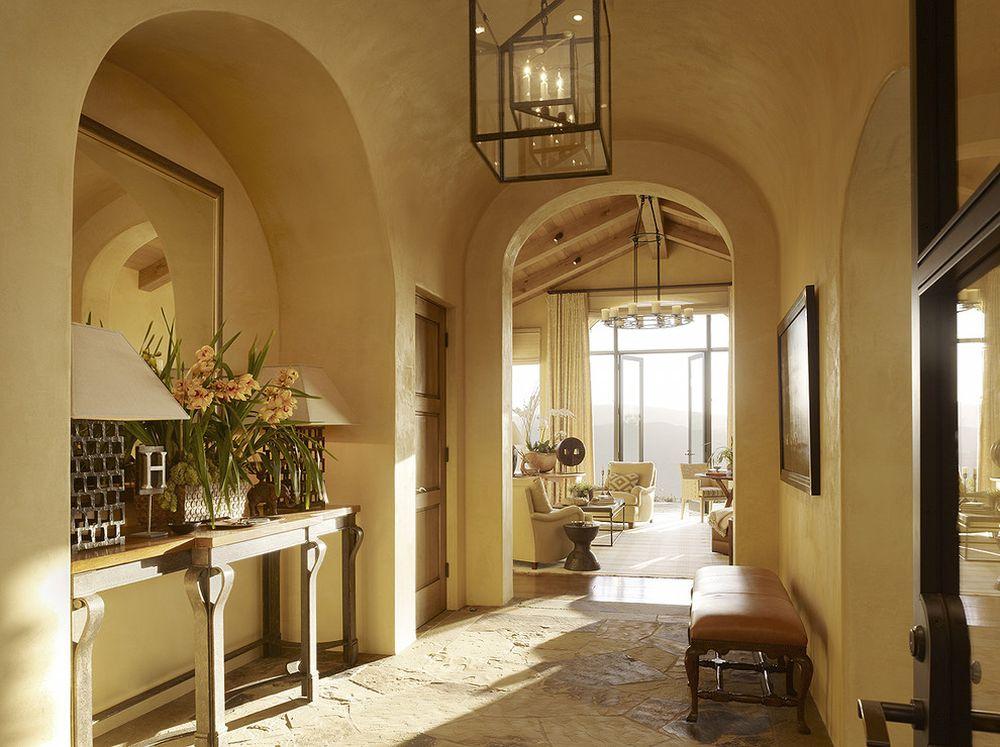 Încă de la intrarea în casă se simte lumina naturală din plin, grație deschiderilor existente. Pardoseala din piatră parcă face tranziția dintre exterior și interior, unde pereții sunt finisați cu o tencuială decorativă ce are un aspect natural. Înălțimea generoasă a spațiilor face ca ele să fie percepute ca fiind mult mai generoase.