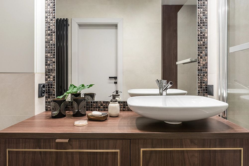 Baia s-a dorit mai elegantă, iar acest lucru este sugerat prin mobilier, forma lavoarelor și mozaicul din sticlă folosit în amenajare. Suprafața mare a oglinzii dă impresia de spațiu mai generos și mai luminos într-o baie simplă de bloc.