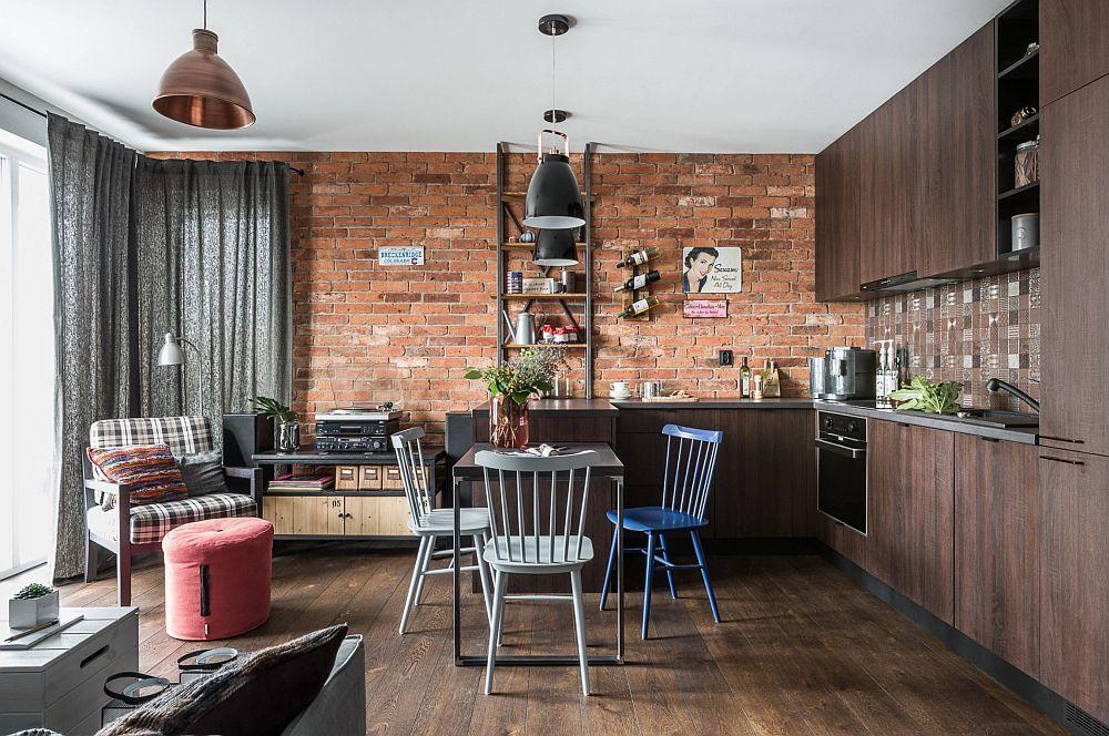 La intrarea în zona de zi bucătăria este cea care domină spațiul. Peretele îmbrăcat cu cărămidă aparanetă atrage atenția, iar pentru senzația de spațiu acesta nu a fost aglomerat. O singură etajeră se citește pe suprafața lui, scopul fiind dublu - pentru depozitare, dar și estetic pentru a crea senzația de simetrie.