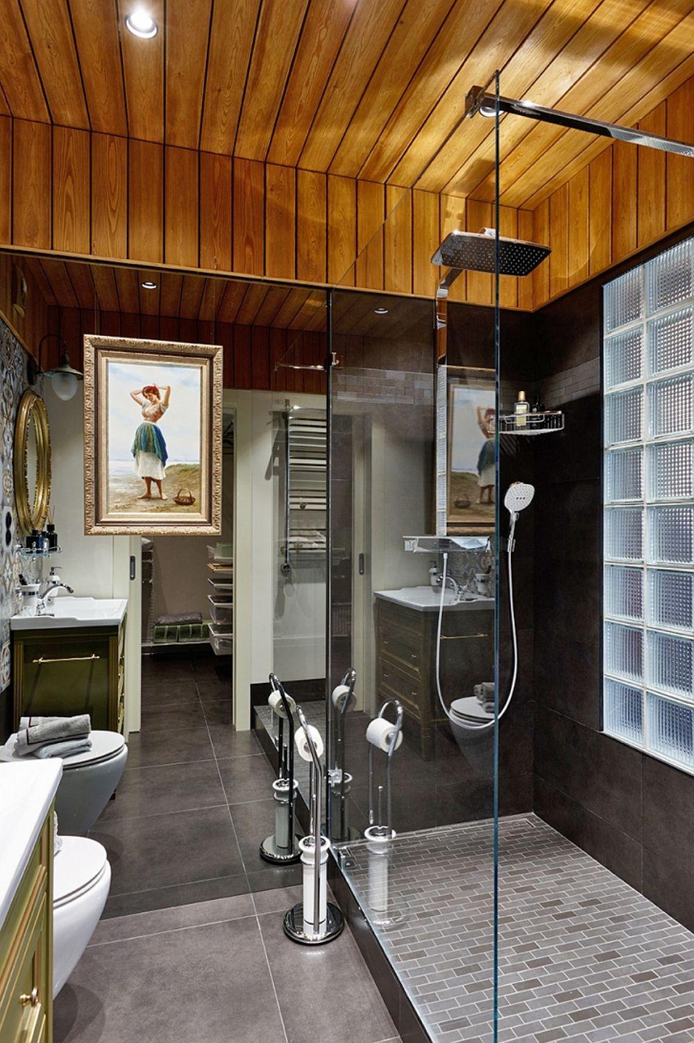 Camera de baie are un întreg perete placat cu oglinzi, ceea ce schimbă perspectiva asupra camerei. De remarcat cărămizile din sticlă care sunt înglobate în peretele comun cu dormitorul. Ele se află în zona de duș. De asemenea, este interesantă placare de la nivelul plafonului prin care s-a inserat un element cald în amenajare.