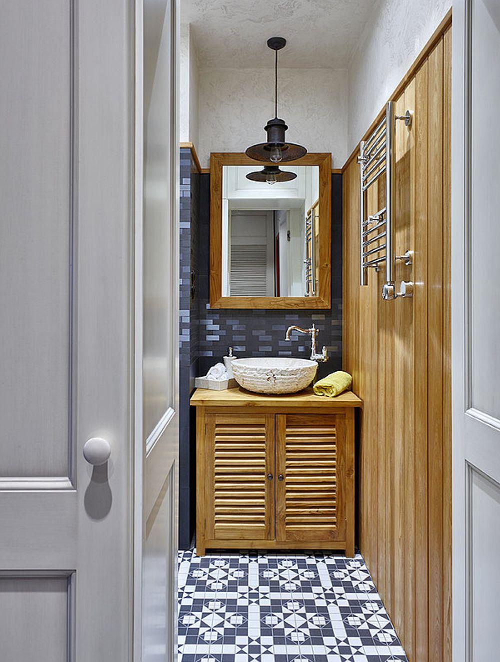 Baia mică, mai exact wc-ul se serviciu este mascat cu o ușă continuată cu o placare care are același desen. Totul gândit la interior în alb și negru, dar prezența lemnului dă un ton armonios și cald amenajării cu tușe industriale. Pardoseala din hol este continuată și în acest spațiu.