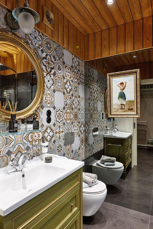 Pentru a aduce note colorate ambientului băii, designerul a prevăzut ca un alt perete să fie placat cu ceramică de tip patchwork, iar mobilierul de baie să fie finisat într-o nuanță plăcută de verde. Tabloul și oglinda dau o notă elegantă și eclectică băii prin ramele lor aurii.
